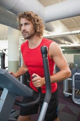 Determined man working out on x-trainer in gym