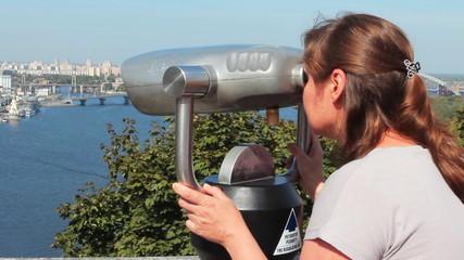 woman watching in huge binocular on viewing platform, closeup
