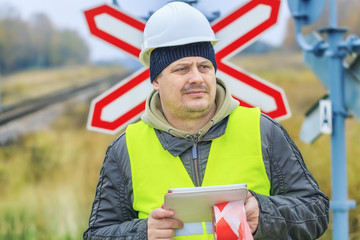Railway engineer with tablet PC near warning signs