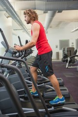 Side view of man working out on x-trainer in gym
