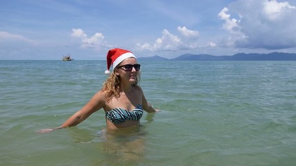 Woman in Santa Hat on the Sea Beach. Christmas or New Year. Slow