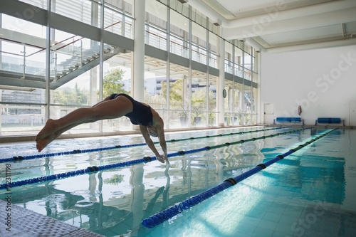 canvas print picture Fit swimmer diving into the pool at leisure center