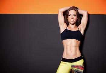 beautiful girl in a gym near gray orange wall