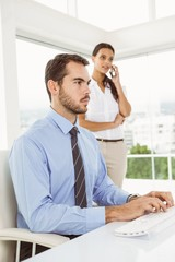 Businessman using computer while woman on call