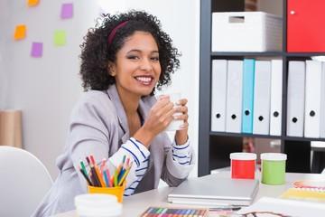 Female interior designer with coffee cup at desk