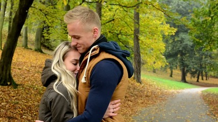 woman cuddles to men - model happy couple in love - autumn park