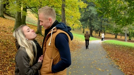 young model couple in love plays - autumn park- couple kiss