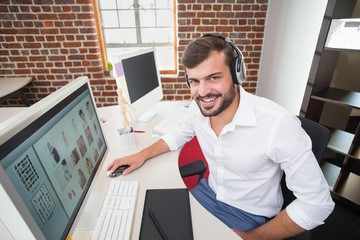 Smiling photo editor using computer in office