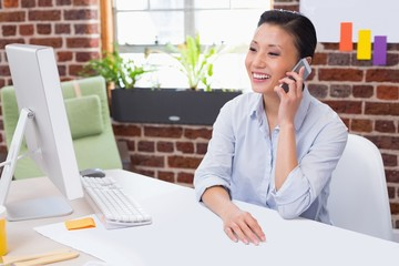 Female executive using mobile phone at desk