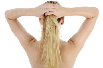 Blonde Frau richtet Frisur zu Pferdeschwanz