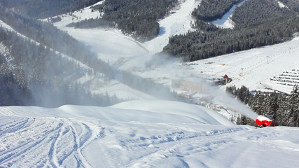 snow gun shoots at snowy mountains in winter