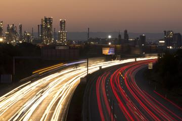 Autobahn bei Nacht mit Lichtspuren u Stadt im Hintergrund zu Son