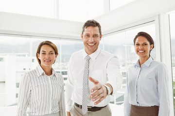 Businessman with colleagues offering handshake at office