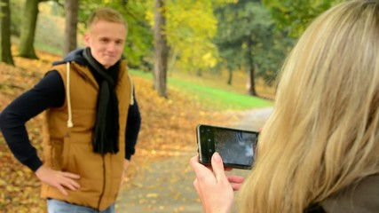woman photographing man with smartphone - happy couple-park