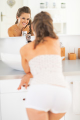 Smiling young woman standing in bathroom and looking in mirror