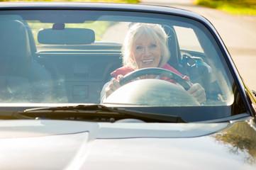Attraktive Seniorin fährt offen im Cabriolet