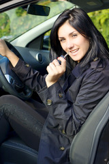 Happy woman in car with key in hand