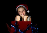 a pretty little girl opens her Christmas present
