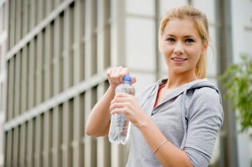 Junge, sportliche Frau öffnet Wasserflasche