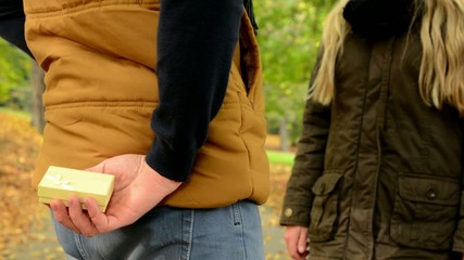 man gives a gift to woman - happy couple in love - autumn park