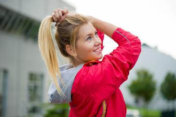 Junge Sportlerin bindet ihren Zopf