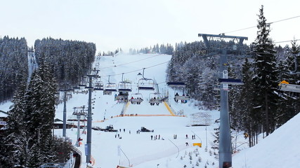 long ski lifts moving above sky slopes in winter forest