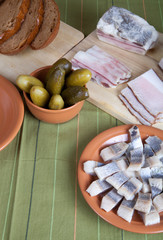 Herring, bread, pickles and bacon on a green napkin