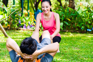 Asian coach helping man with stretching exercises