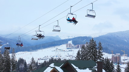 ski lifts with skiers above roofs of hotels in winter mountains
