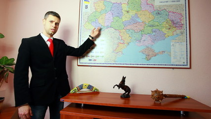 handsome young manager giving presentation near huge map on wall