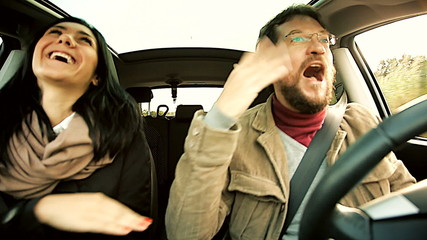 Couple having fun dancing in car happy