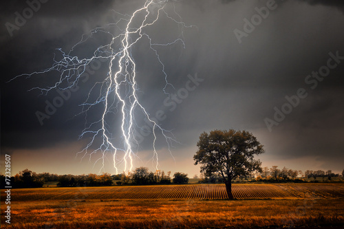 Fotobehang Platteland Lightning over field