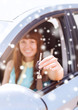 close up of smiling woman with car key outdoors