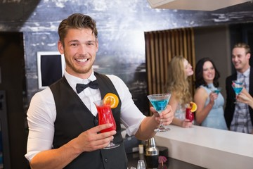 Handsome barman smiling at camera holding cocktails