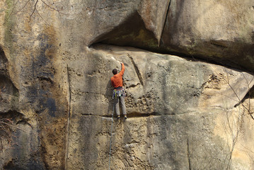 Male climber climbing rock face