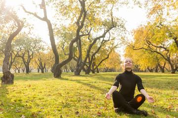 Woman doing yoga in autumn park