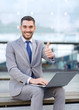 smiling businessman working with laptop outdoors