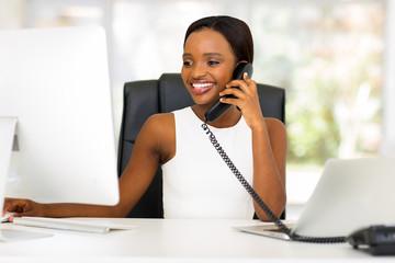 african businesswoman talking on landline phone