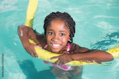 Leinwanddruck Bild Cute little girl swimming in the pool