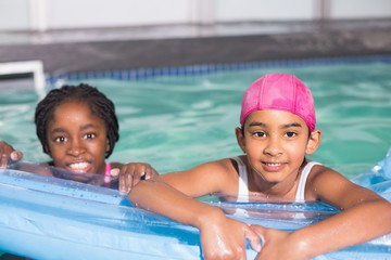 Cute little girls swimming in the pool