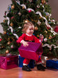 Cute Baby Girl in Santa costume opening the present near Christm