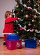 Cute Baby Girl in Santa costume decorating Christmas tree