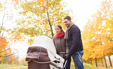 smiling couple with baby pram in autumn park