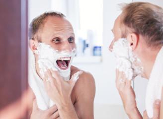 Happy man shaving in bathroom