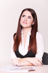 Portrait of beautiful young business woman sitting at desk at of