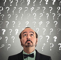 businessman with many questions above head looking up