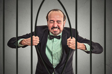 middle aged stressed businessman bending bars of his prison