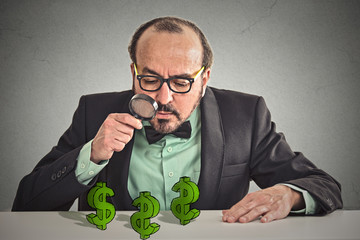 Business man looking through magnifying glass at dollar signs