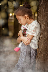 Charming little girl in forest with  doll