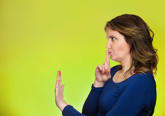 woman with finger on lips, shhh gesture asking be quiet